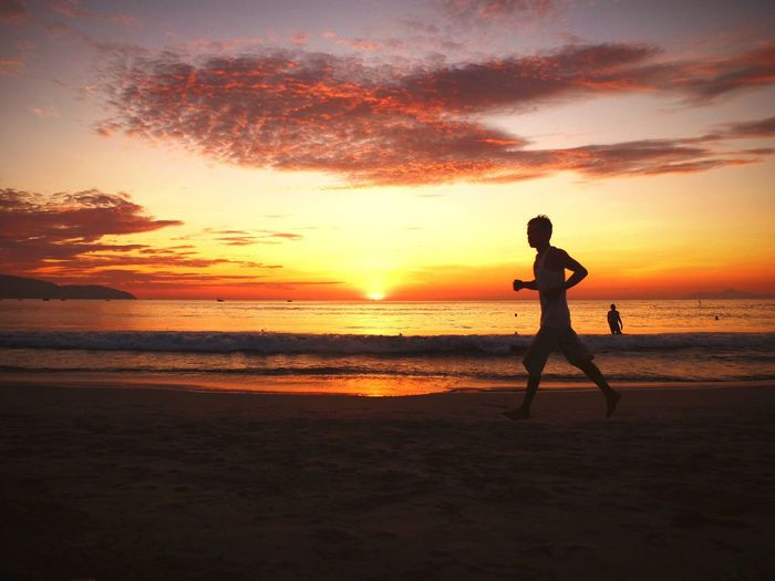 Sunset Beach Sea Silhouette Orange Color Full Length Scenics Sky Shore Water Nature Real People Beauty In Nature One Person Sand Leisure Activity Vacations Horizon Over Water Lifestyles Cloud - Sky danang Be. Ready.