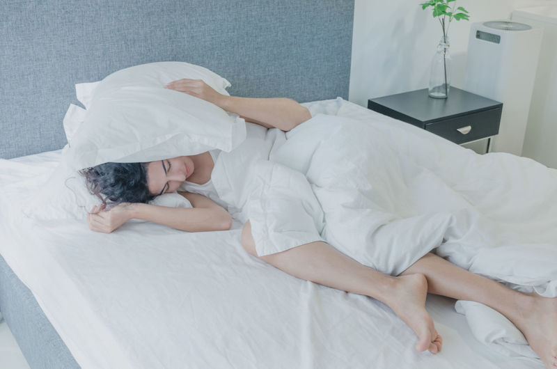 Woman covering ears with pillows while sleeping on bed
