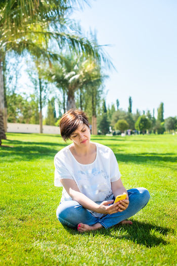 Full length of woman using smart phone while sitting at park