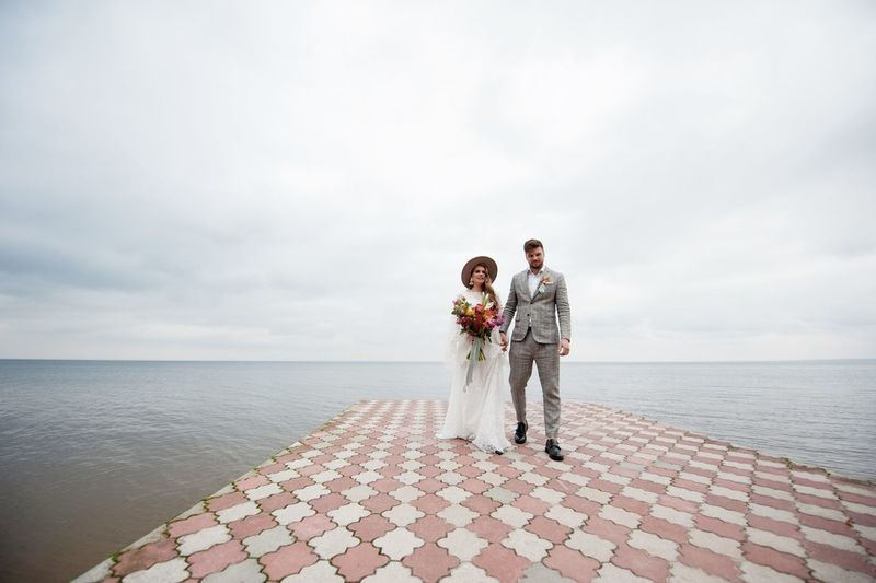 Couple walking on pier over lake against cloudy sky