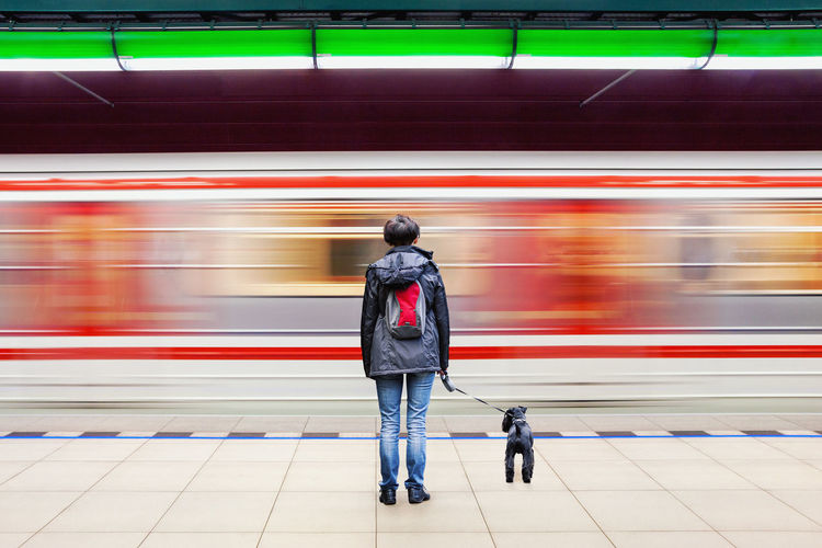 Woman with dog in subway station with blurry moving train in background