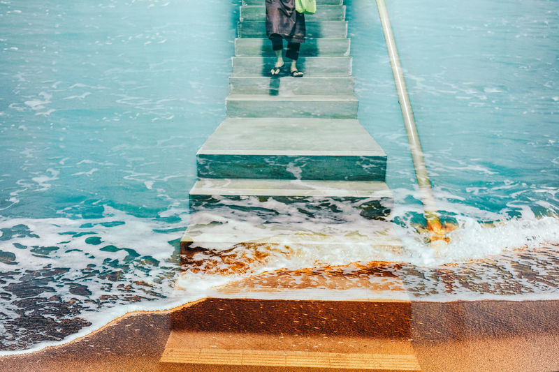 Low section of person walking on steps by sea