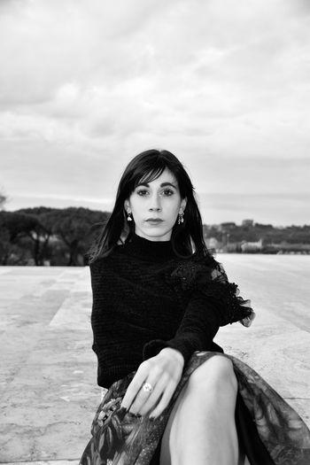 Portrait of woman sitting against sky