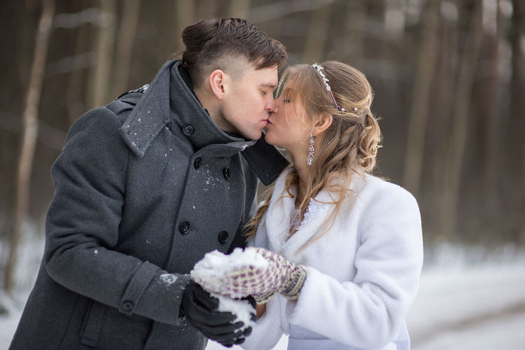 Couple With Snow Kissing During Winter