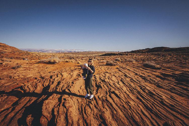 Full length of man on arid landscape against clear sky