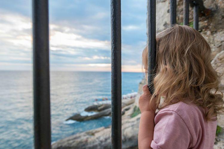 Girl looking through window at sea against sky
