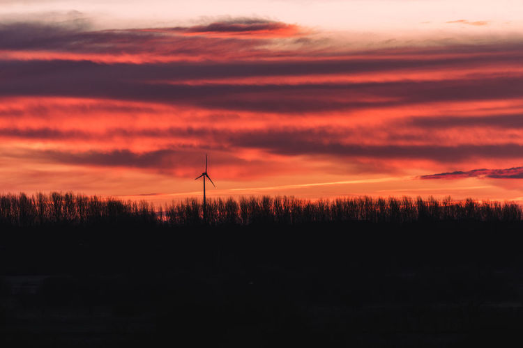 Alternative Energy Beauty In Nature Cloud - Sky Environment Environmental Conservation Fuel And Power Generation Landscape No People Orange Color Renewable Energy Scenics - Nature Silhouette Sky Sunset Sustainable Resources Tranquil Scene Tranquility Tree Turbine Wind Power Wind Turbine