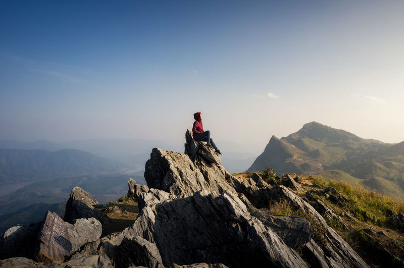 Side view of woman sitting on mountain against blue sky