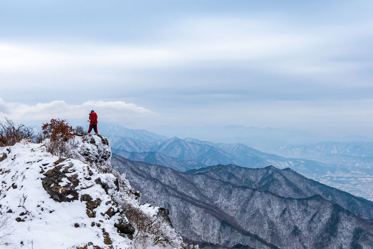 Rear View Of Hiker Standing On Snowcapped Mountain Against Cloudy Sky