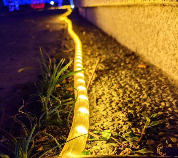 Close-up of yellow illuminated lighting equipment on street at night