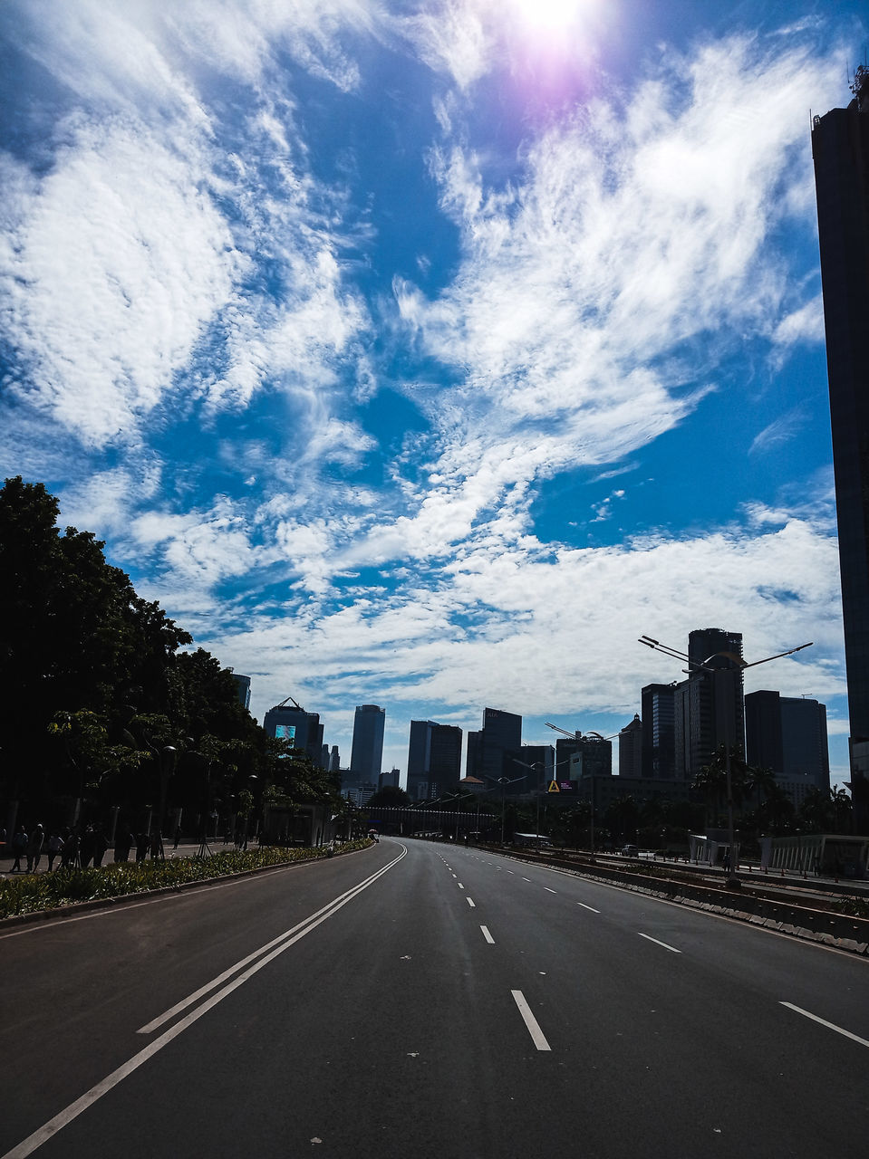 cloud - sky, sky, road, transportation, building exterior, built structure, city, the way forward, direction, architecture, nature, road marking, symbol, marking, no people, building, street, day, sign, diminishing perspective, outdoors, office building exterior, skyscraper, cityscape, dividing line