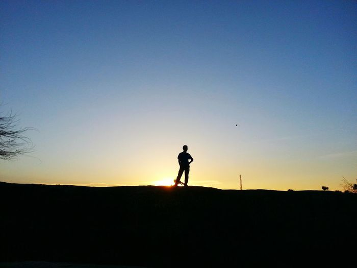 Silhouette man standing on field against clear sky during sunset