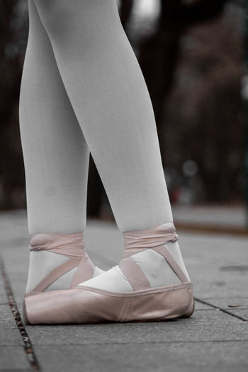 Low section of ballet dancer standing on footpath