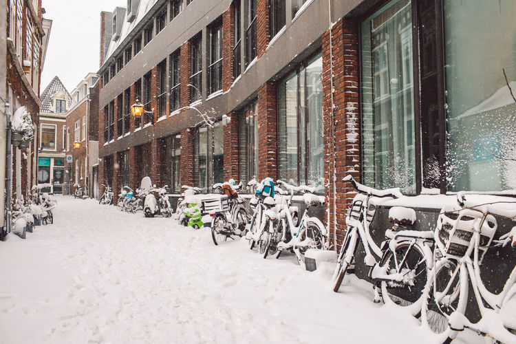Bicycles on street amidst buildings in city during winter