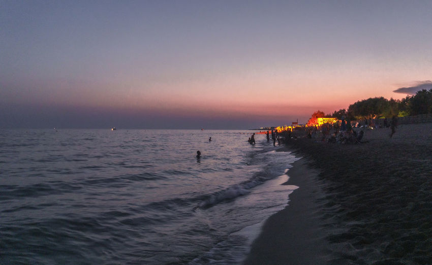 People on beach against clear sky during sunset