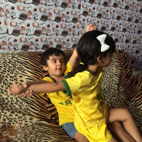 Siblings playing on sofa at home