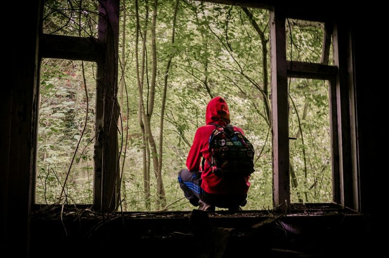Rear View Of Hiker Crouching On Window Of Abandoned House By Forest