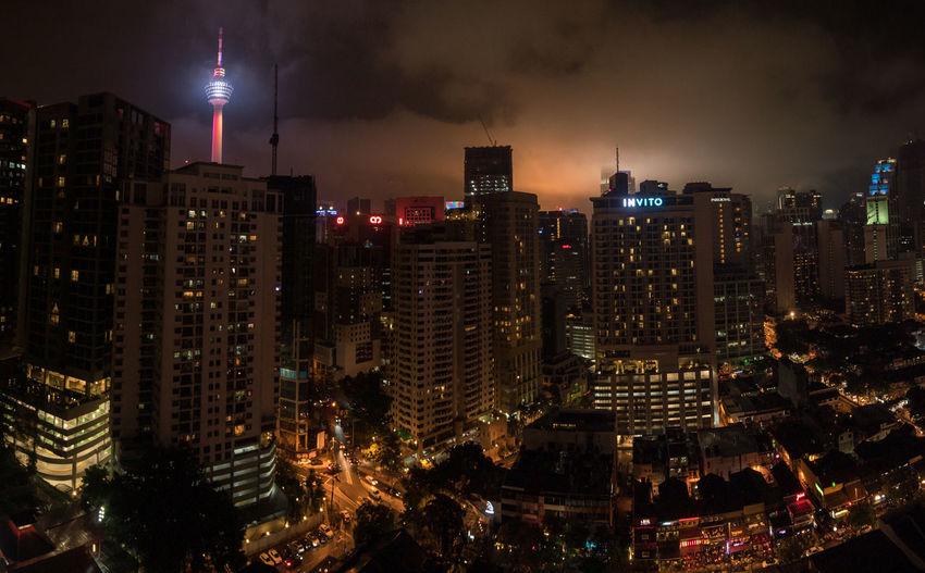 Illuminated menara kuala lumpur tower in city at night