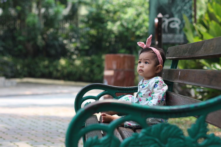Baby Girl Sitting On Bench At Park