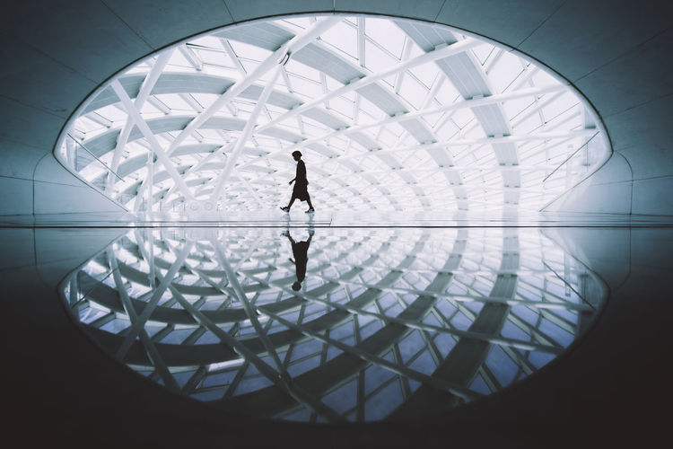 Low angle view of silhouette people walking in glass