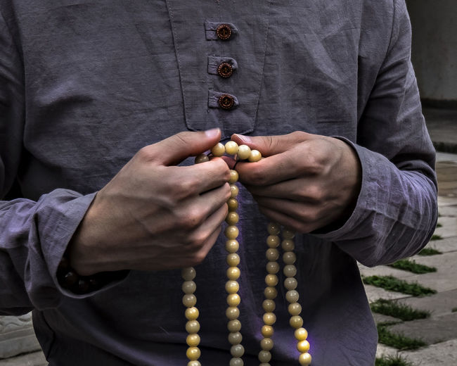 Man holding chain in China d.y China Beauty China Town China Photos Bead Belief Casual Clothing China China City Life China Culture Close-up Clothing Day Front View Hand Holding Human Body Part Human Hand Lifestyles Men Midsection One Person Outdoors Real People Religion Spirituality