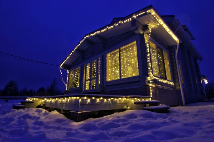 Low angle view of illuminated building during winter at night