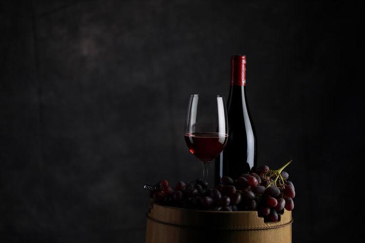 Red wine bottles on table against black background