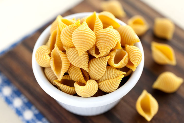 Carrot Conchiglie Pasta. Dry pasta bowl. Carrot Pasta Carrot Conchiglie Conchiglie Pasta Italian Pasta Natural Light Blue Napkin Bowl Carbohydrates Close Up Conchiglie Cutting Board Dry Pasta Food Food And Drink Italian Food No People Nutrition Pasta Still Life Studio Photography Wooden Background