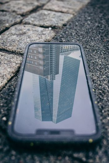 High angle view of phone with modern building reflection on footpath