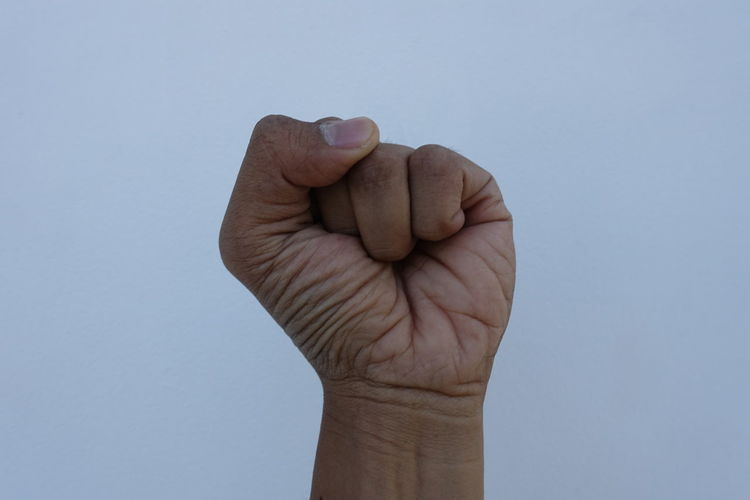 Cropped hand clenching fist against blue sky