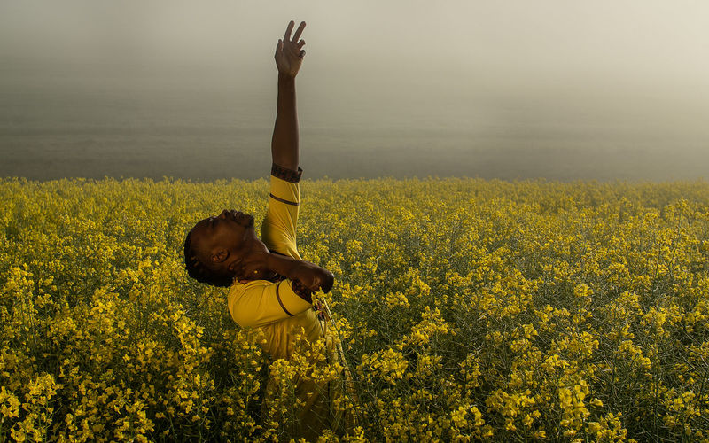 Man with arms raised standing on yellow flower field