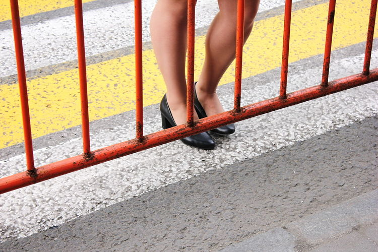 Low section of woman standing on railing