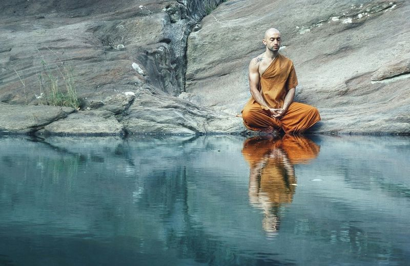 Reflection of monk meditating on lake
