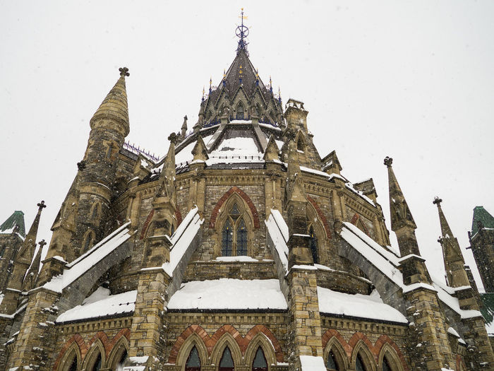 The beauty of The Library of Parliament in the snowfall, Ottawa - capital of Canada Architecture Built Structure Building Exterior Sky No People Building Nature Outdoors Low Angle View Day Tower Historic Historical Building History Government Politics And Government Politics Democracy Icon Landmark Snow Cold Temperature Winter Snowing Library Parliament Building Daylight City Cityscape Beauty Colors Cold