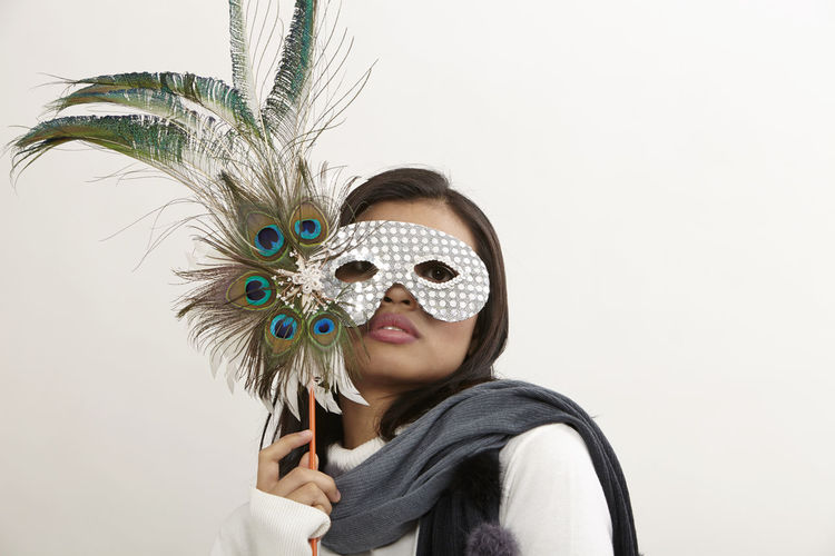 Portrait of young woman wearing eye mask holding peacock feathers against white background