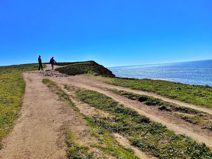 A glorious couple walks along divided ocean headland paths. Couple Man Woman Path Dirt Soil Upward Climbing Two Dual Golden Sandstone Headlands Zen Background Peaceful Tourist View Overlook Edge Waves Therapeutic Working Clear Sky Rural Scene Manual Worker Occupation Sky Landscape