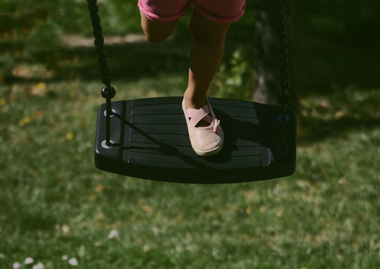 Low section of person on swing in playground