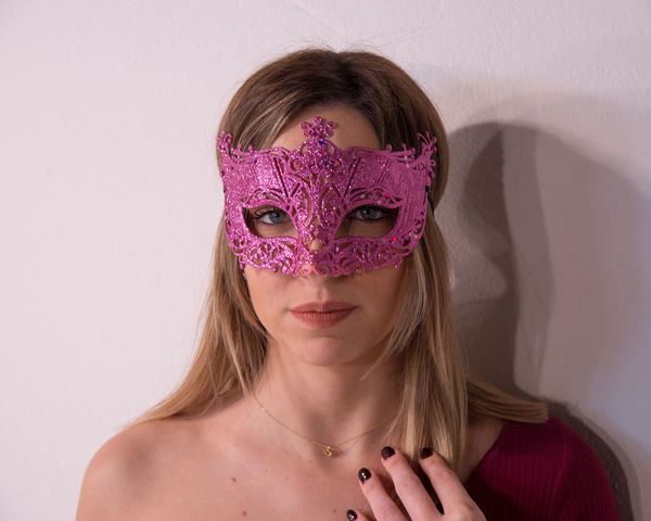 Blonde girl with carnival mask over white background. Masquerade. Portrait of Beautiful Blond Woman in a Carnival Mask. Masquerade. Girl. Beauty & Fashion Adult Blond Hair Childhood Children Only Close-up Day Disguise Eye Mask Front View Headshot Looking At Camera One Person People Portrait