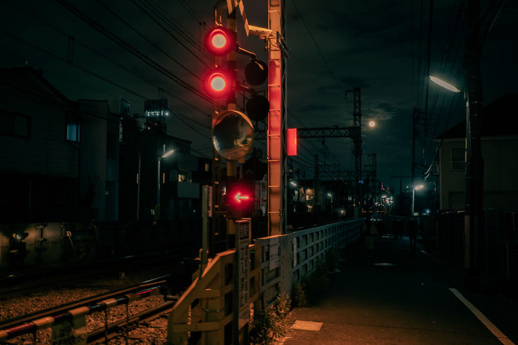 Train on illuminated railroad station platform at night