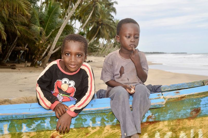Portrait of cute boys sitting on fishing boat at beach