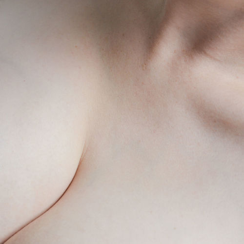 Close-up of shirtless woman against white background
