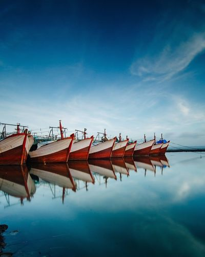 Boats Moored In Lake Against Blue Sky