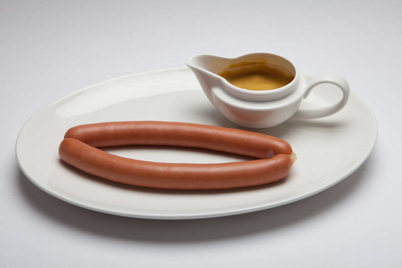 High Angle View Of Sausage With Dip Served In Plate On Table