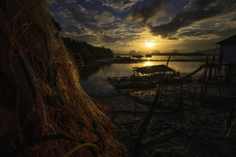 Fishing net at beach against sky during sunset