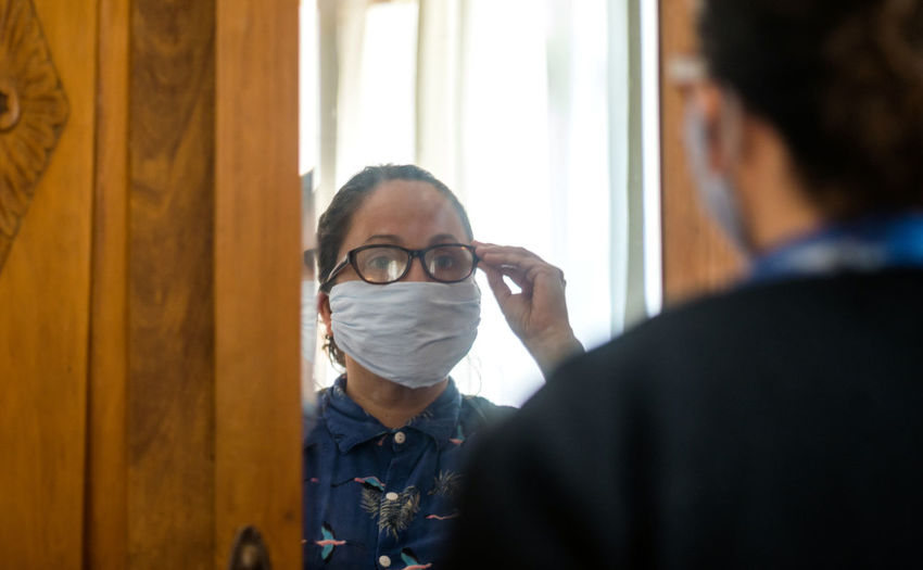 Woman wearing mask and eyeglasses while looking in mirror