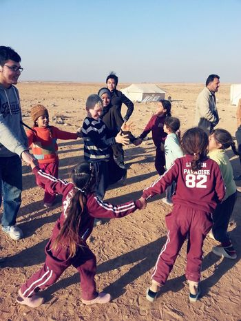 Group of young humanitarians playing with Syrian children refugees in Huwajya Camp Real People Outdoors Cultures Sunlight Sand Desert Day Full Length Sky Men Refugees Syrian People