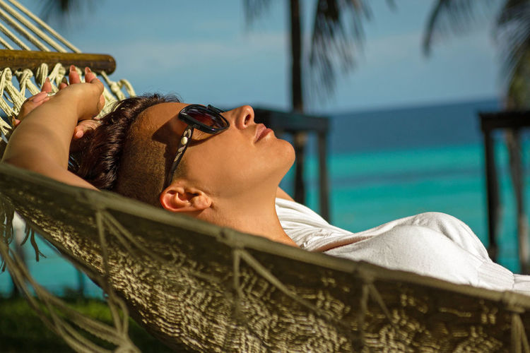 Side view of woman lying in hammock at beach