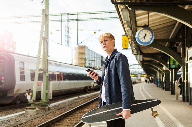 Man standing by train at railroad station platform