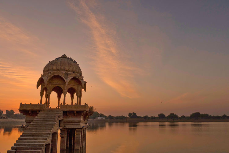 Sunrise over stone tower and historical building in Gadi Sagar lake, Jaisalmer, India. Ancient Civilization Architecture Building Exterior Built Structure Cloud - Sky Gadisagar Temple Gadisarlake History Jaisalmer Lake Nature No People Orange Color Reflection Religion Sky Sunset The Past Tourism Travel Travel Destinations Water