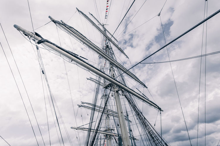 Low angle view of sailboat against cloudy sky